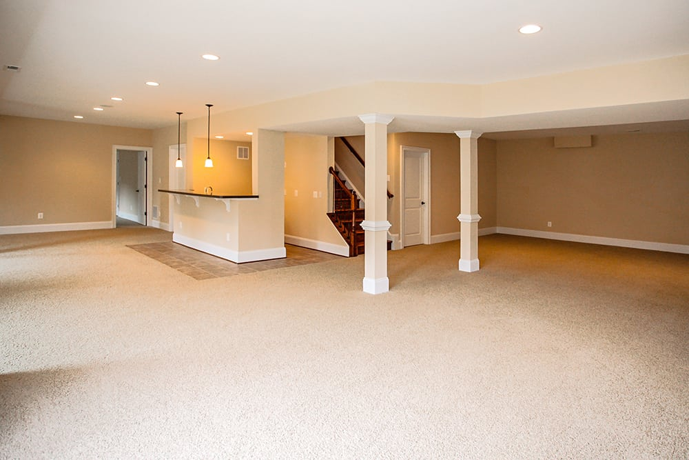 Large carpeted Warrenton house basement with bar and hanging lights