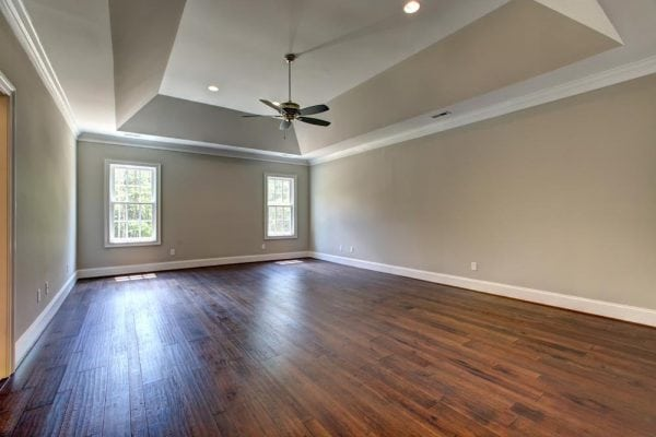 Large room in Haymarket home with two windows, fan, and darker stained wood floors