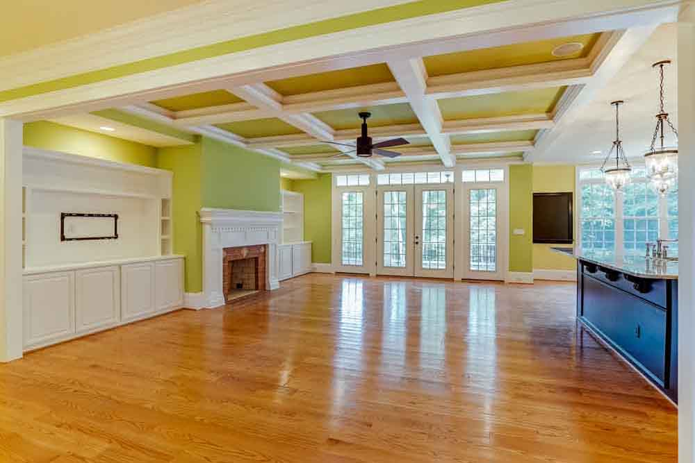 Large space in McLean home next to kitchen with green walls and lattice-like ceilling