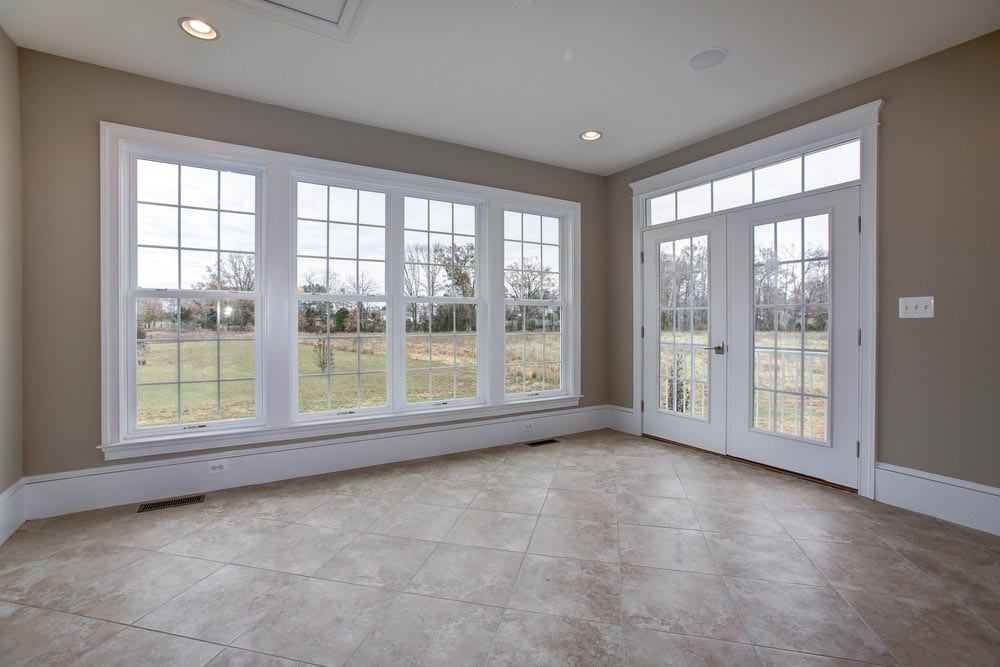 Large stone tiled room with many large windows and glass paneled door