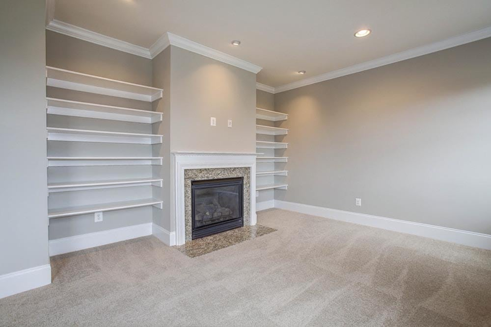 Large white carpet room with many windows and light gray walls and a gas fireplace in Culpeper home