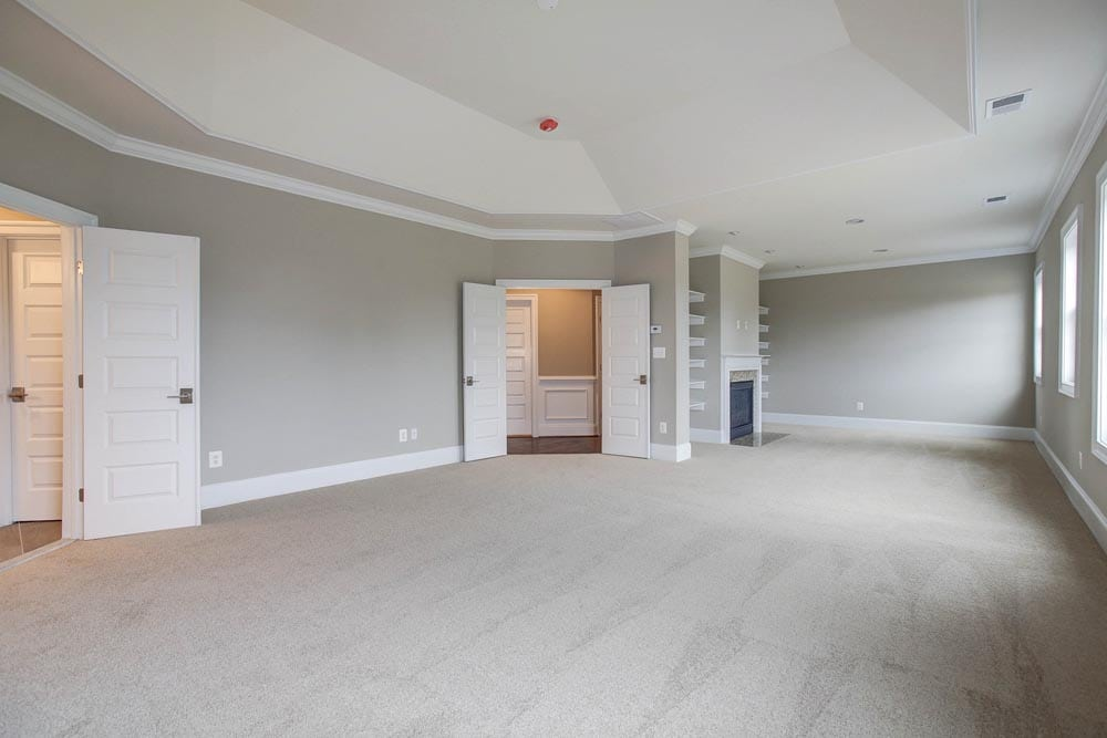 Large white carpet room with many windows and light gray walls and double doors in Culpeper home