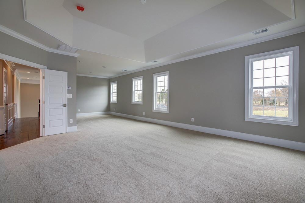 Large white carpet room with many windows and light gray walls in Culpeper home