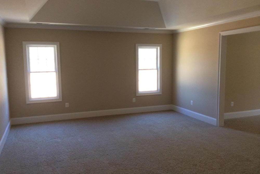 Large white carpet room with two windows in Round Hill home