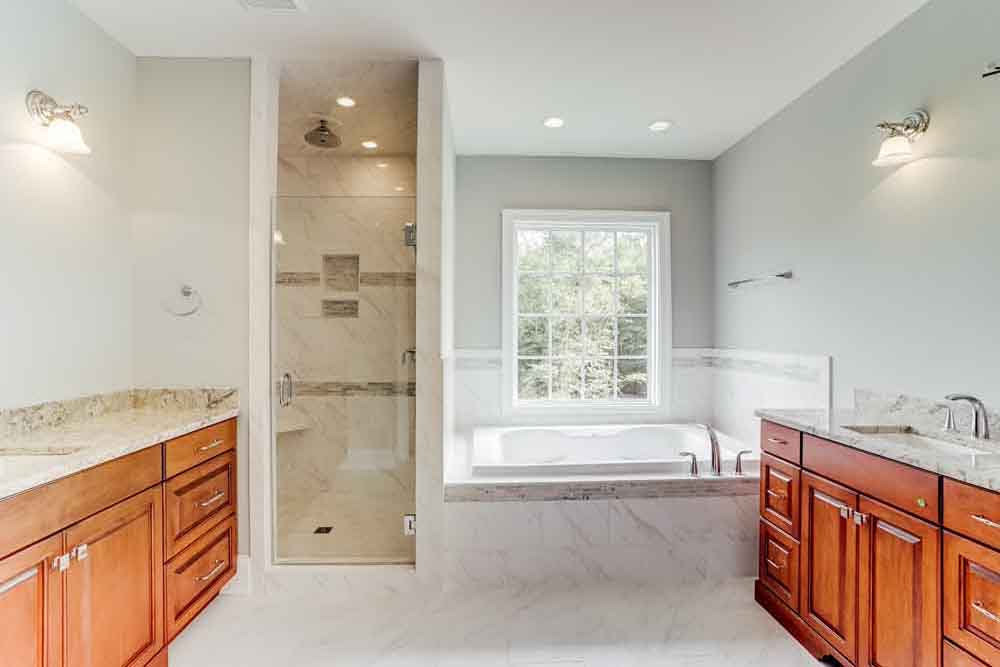Large white marble bathroom in McLean home with shower room and then tub in main area