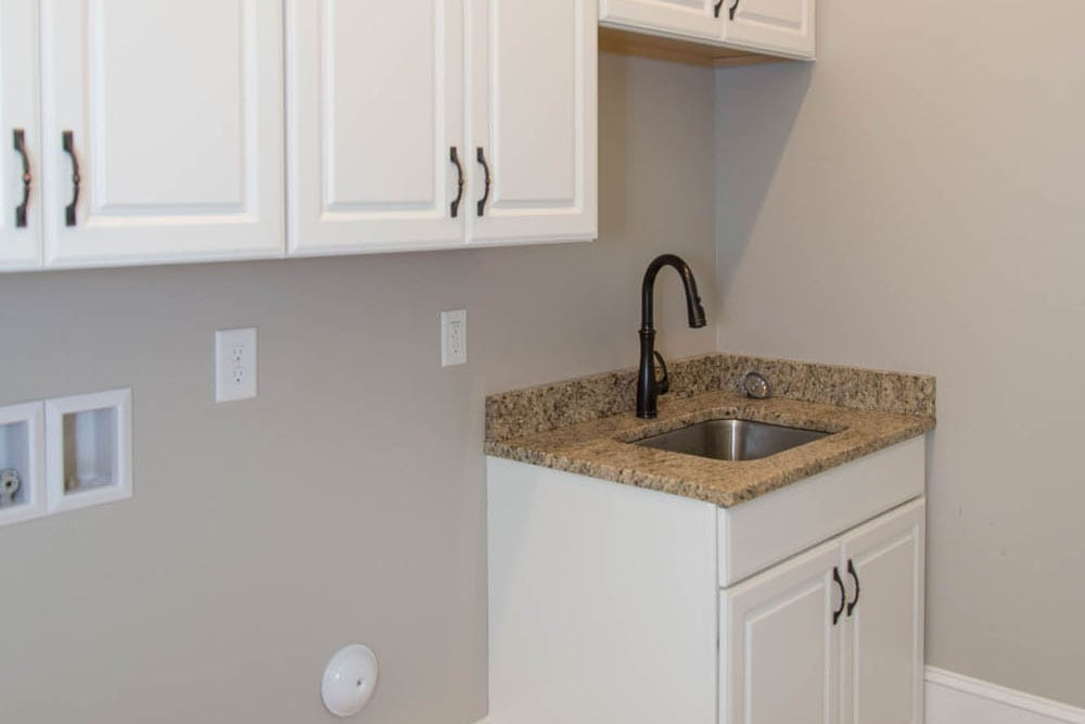 Laundry room in Fairfax home with sink and white cabinets