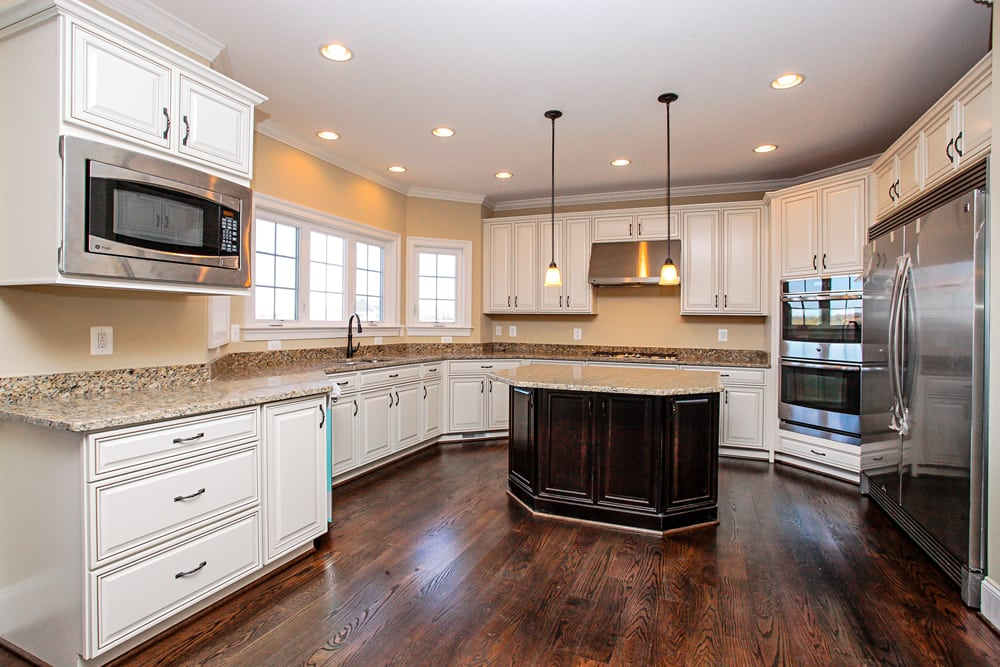 Leesburg home kitchen with hanging lights, white cabients, microwave, and double door refrigerator