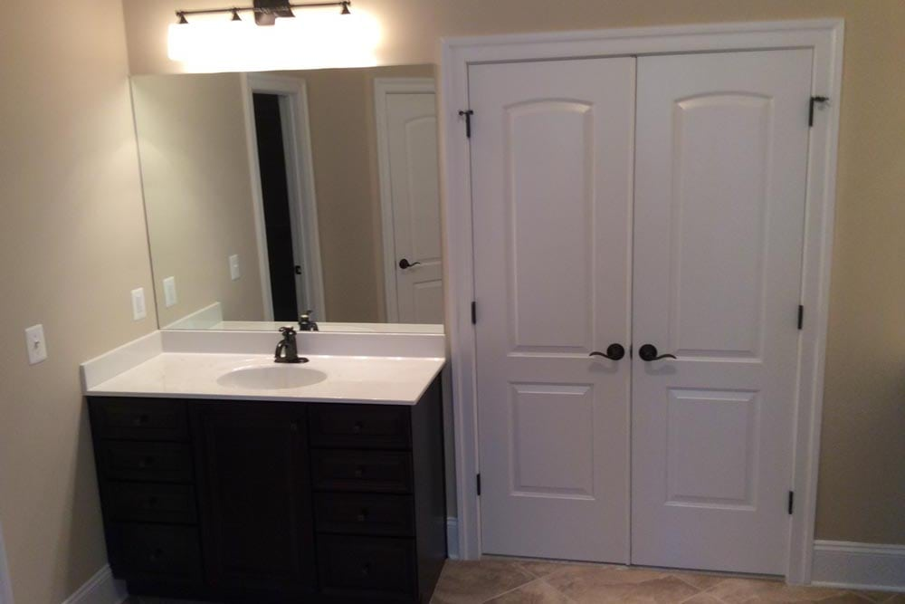 Left side of bathroom in Round Hill home with one white countertop sink and a double door closet