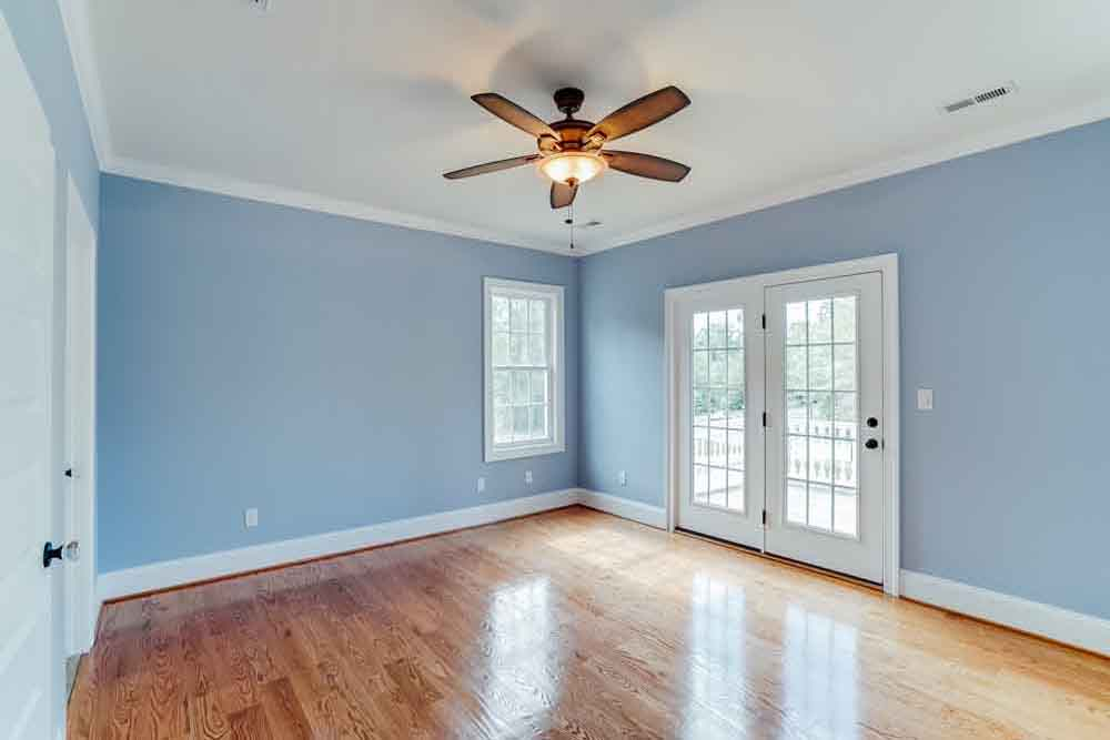 Light blue room in Middleburg home with ceiling fan and glass door leading outside