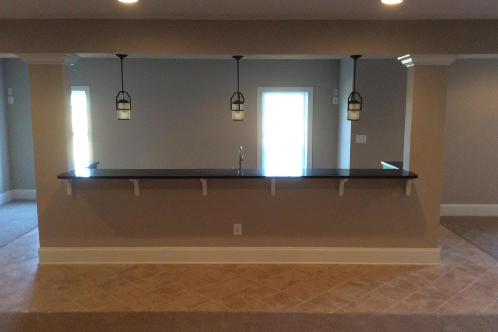 Long basement bar with hanging lights in a house on The Plains