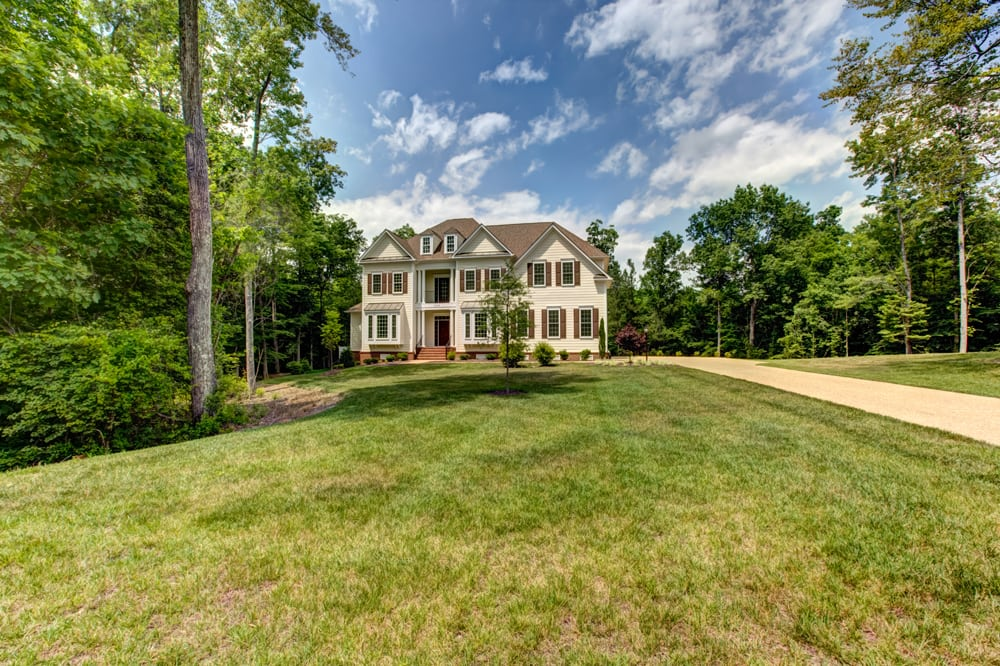 Long driveway leading up to white slatted Ashburn home
