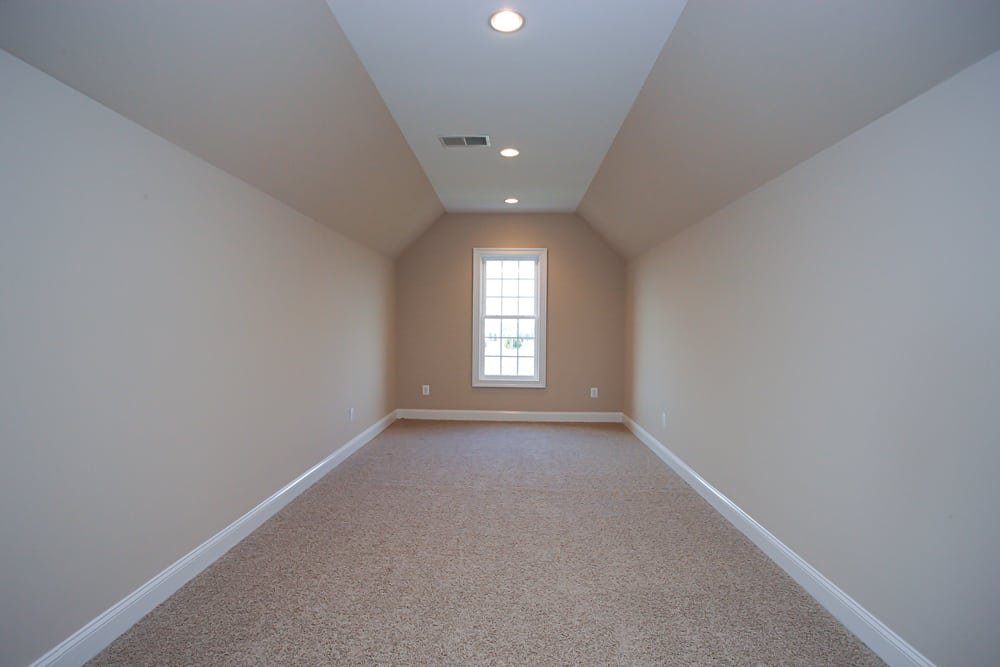 Long room with slanted ceiling and white carpet in Nokesville home