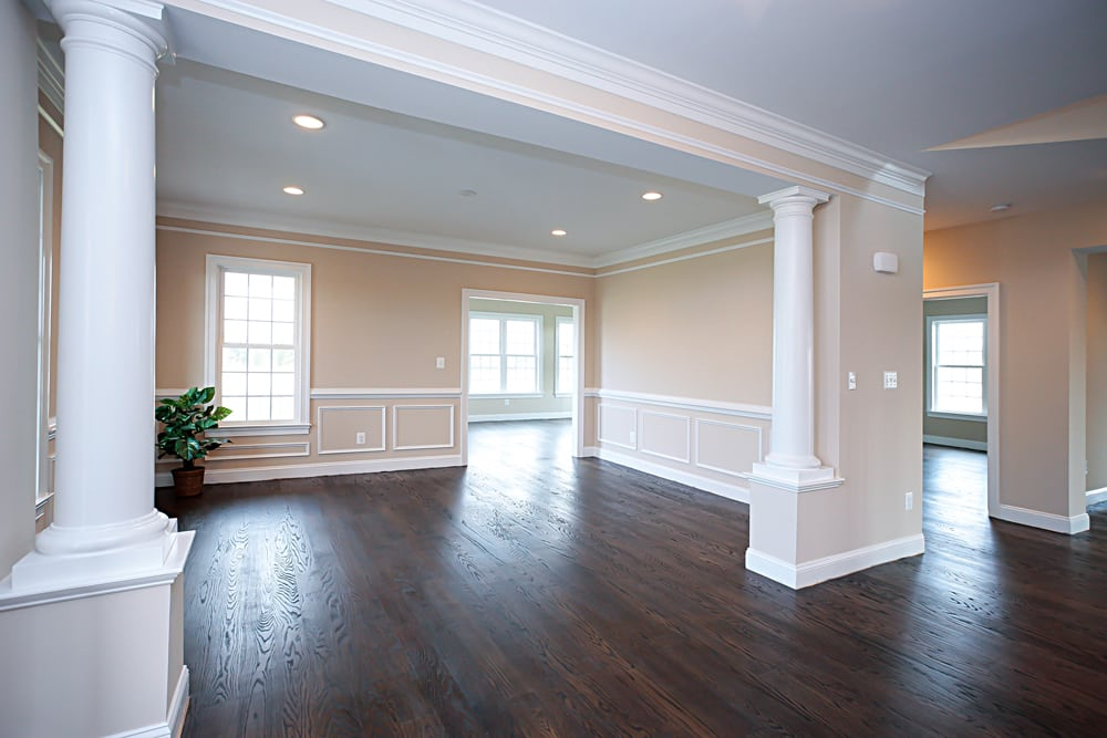 Main area inside Nokesville home with stained floors, small wall pillars, and light pink walls
