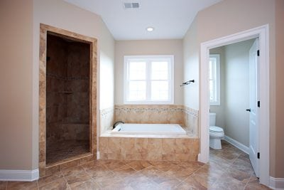 Master Nokesville home bathroom with shower room, bathtub with window above it, and toilet room