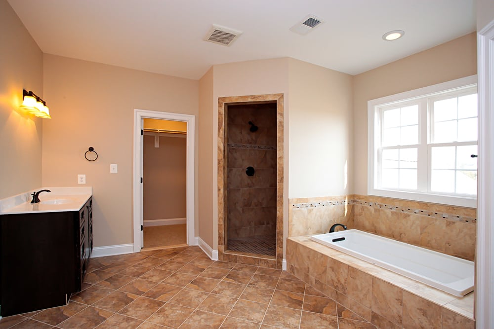 Master bathroom in Nokesville home with shower room, bathtub, and brown stone floors
