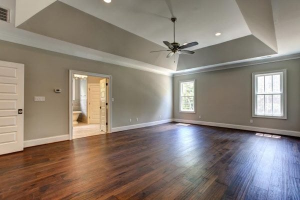 Master bedroom in Haymarket home with two windows, ceiling fan, and bathroom attached