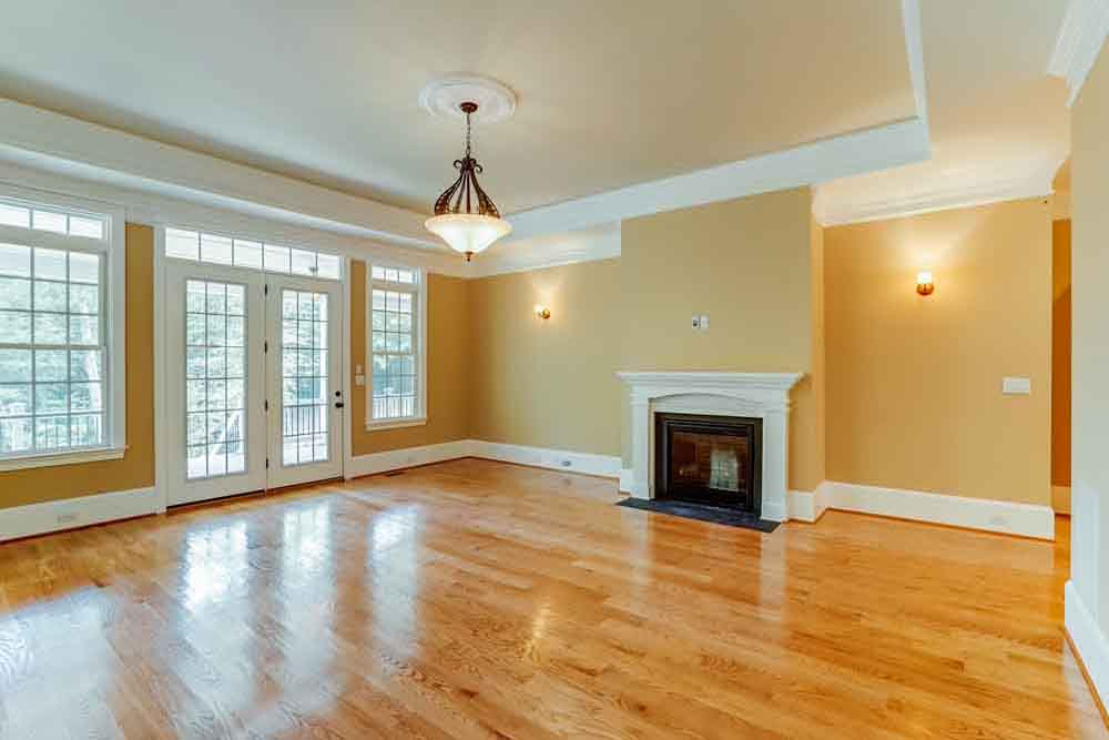 McLean room with light brown wood floors and small gas fireplace room with windows