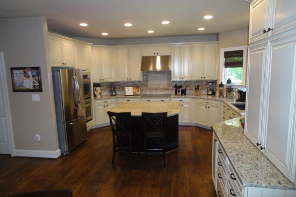 Midland home kitchen with double door refrigerator, island with chairs, stove with hood, and white cabinets