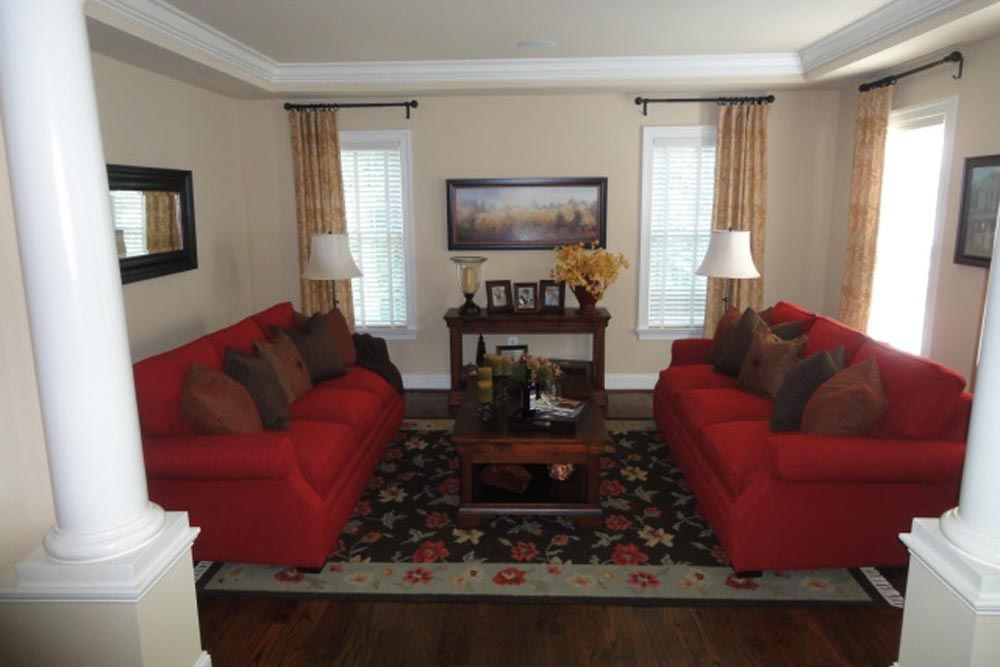 Midland home living room with red couches, windows, and black ornamental rug