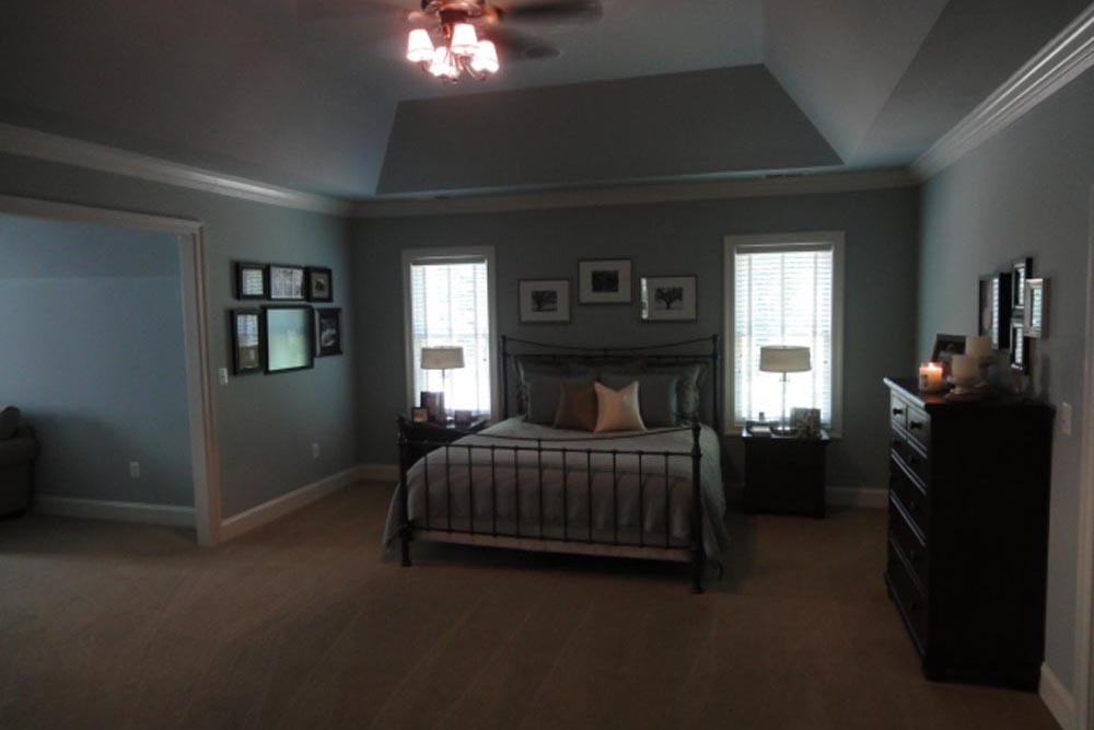 Midland home master bedroom with beige carpet, light blue walls, fan, dark brown chest of drawers, and big bed