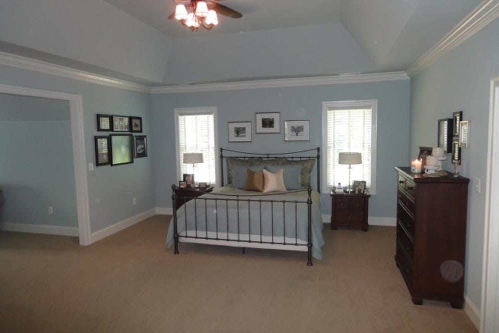 Midland home master bedroom with beige carpet, light blue walls, fan with lights on, and big bed with windows on both sides