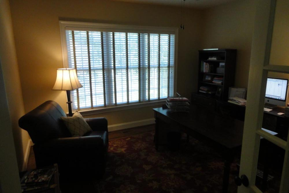 Midland home office with black leather chair, black table, windows, and red ornamental rug