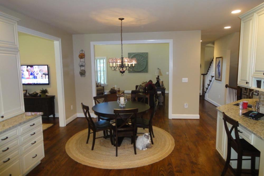 Midland home small dining room with dark brown round table and chairs on top of round beige rug