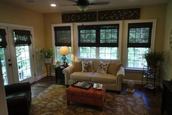 Midland home sunroom with many windows, glass panel door, beige rug and couch, fan, and recessed ceiling lights