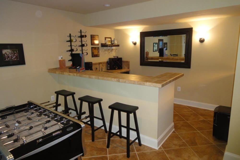 Midlands home basement granite countertop bar with 3 stools and foosball table