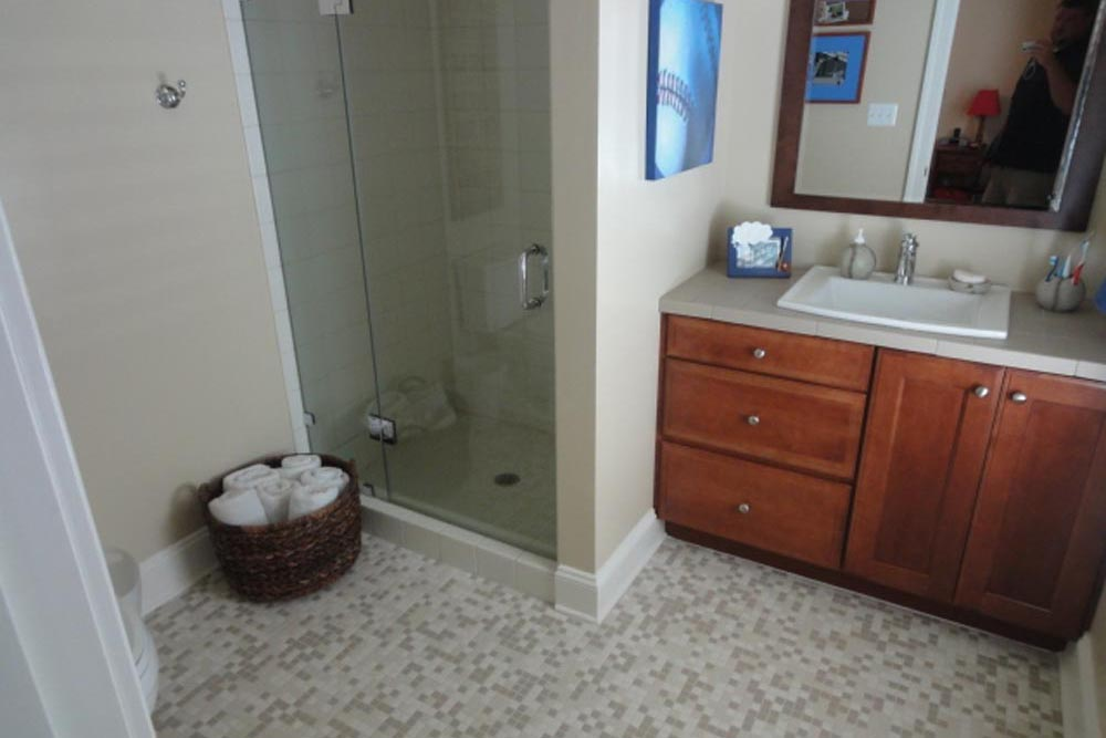 Midlands home bathroom with shower and white countertop sink over lighter brown cabinets