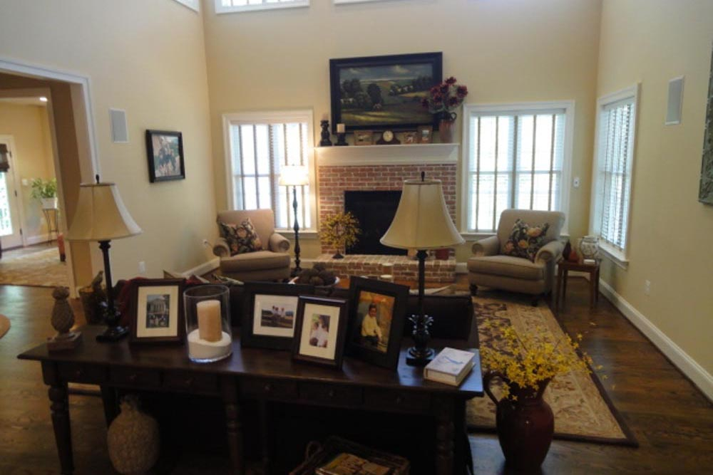 Midlands home den with brick fireplace, ornamental rug, and table with pictures and a lamp