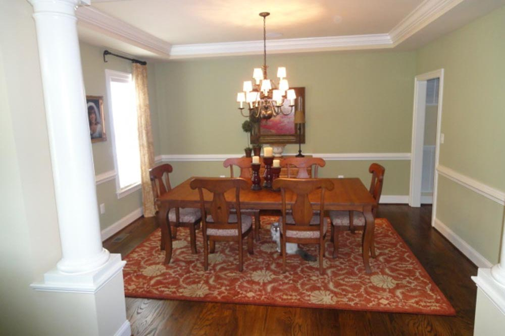 Midlands home dining room with red decorative rug, lighter brown stain chairs and table, with chandelier