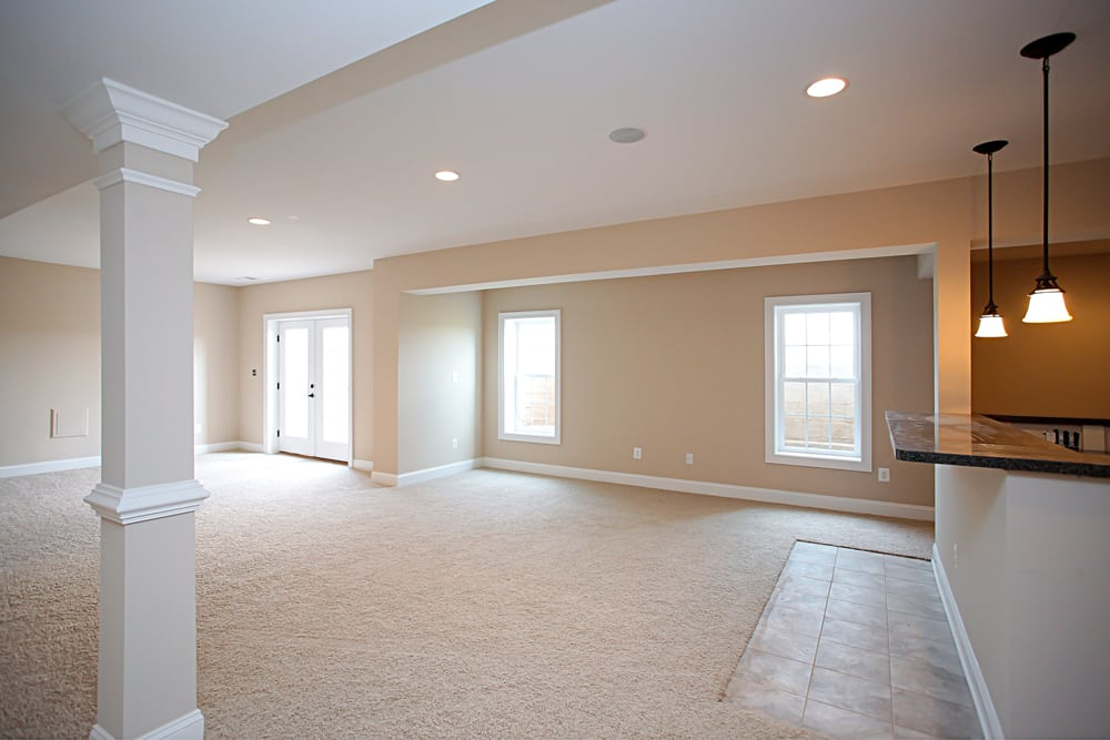 Nokesville home basement with windows, glass panel door, front of bar, and white carpet