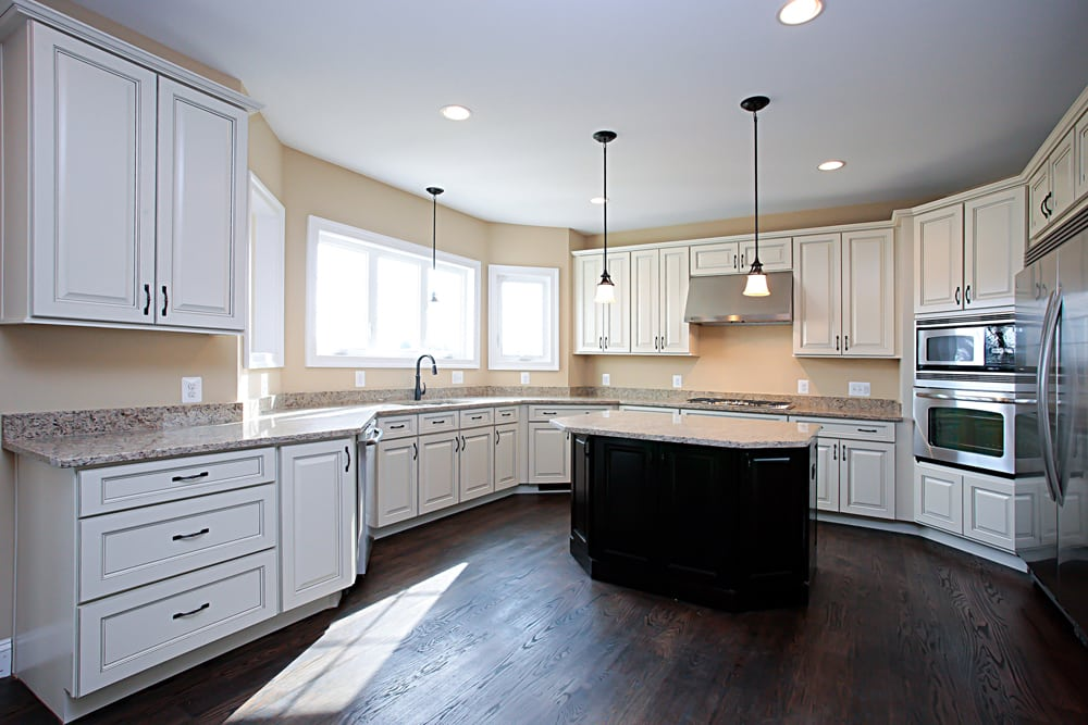 Nokesville home kitchen with white cabinets, island, and hanging and recessed lights