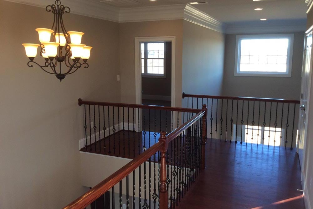Open second floor hallway with chandelier and door in a house on The Plains