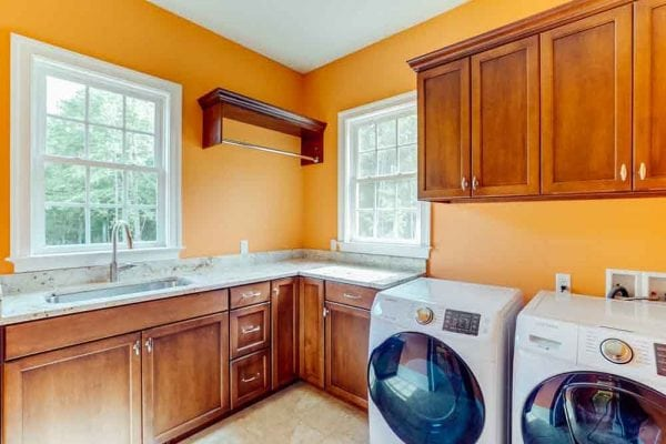 Orange laundry room in Middleburg home with windows and light brown cabinets