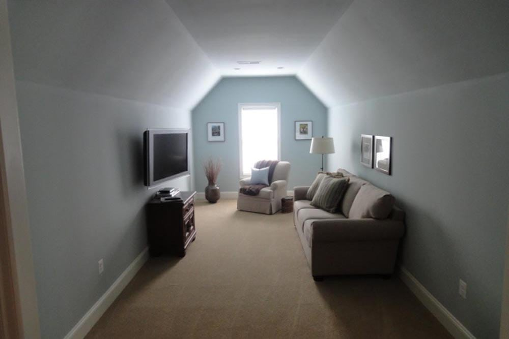 Other side of Midland home master bedroom with couch, tv, chair, and slanted ceiling leading to a window