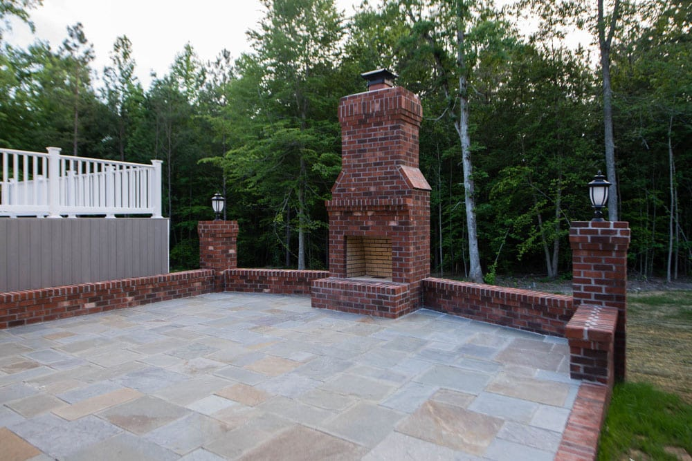 Outdoor light grey tiled patio on Fairfax home with low brick walls and brick fireplace