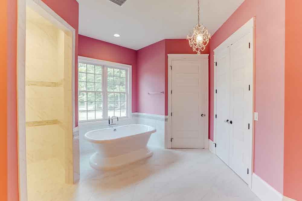 Pink master bathroom in Middleburg home with bathtub in open area, toilet room, and shower room