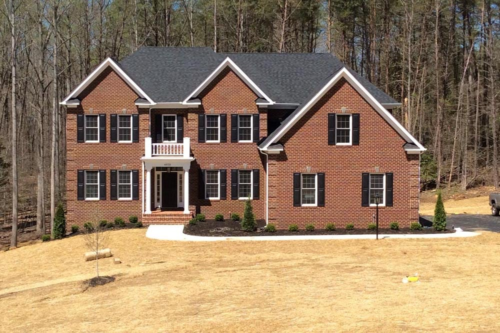 Red brick Round Hill home with dark-color shutters and a small window balcony