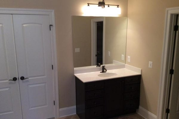 Right side of bathroom in Round Hill home with one white countertop sink and a double door closet