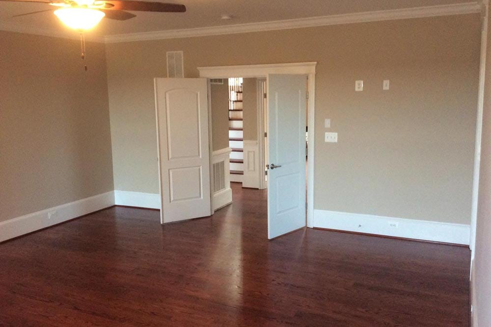 Room in a house on The Plains with dark stained wooden floors, double doors, and a ceiling fan