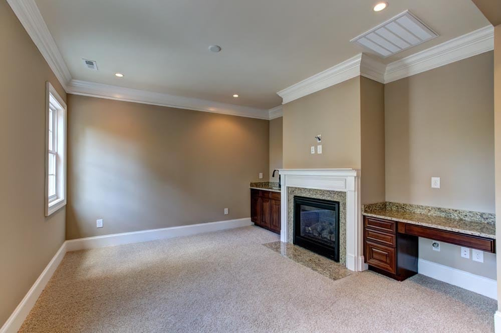 Room with fireplace separating two granite countertop spaces