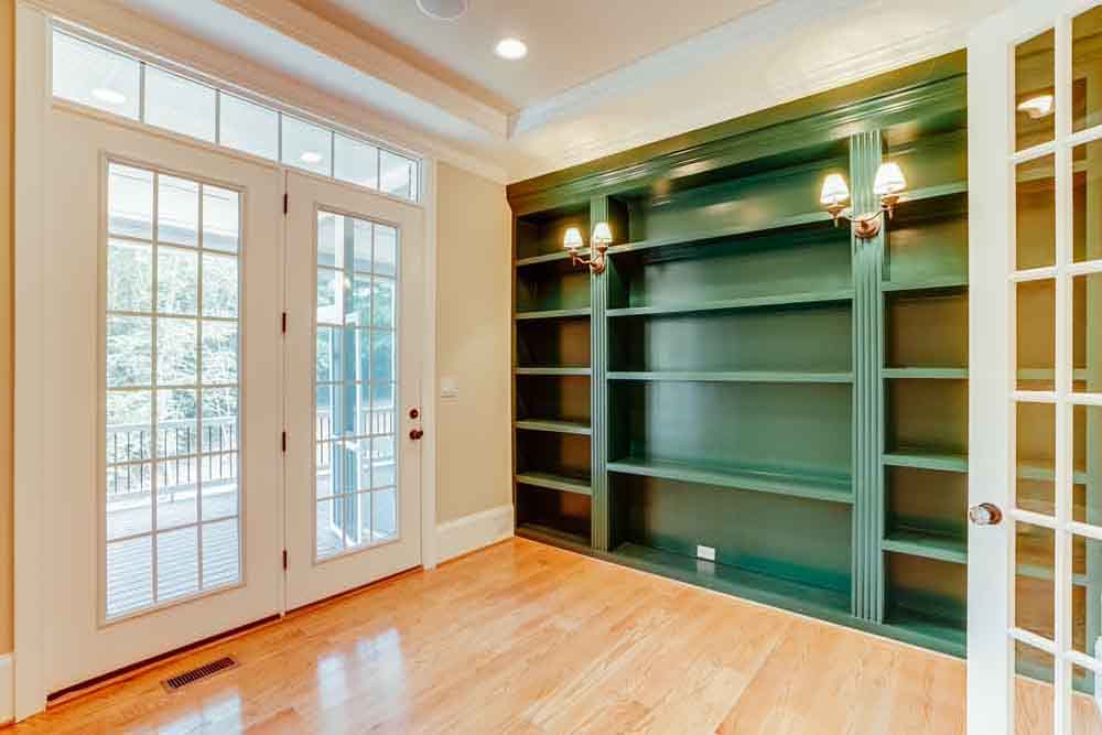 Room with large green bookcase next to glass paneled double doors in Middleburg home