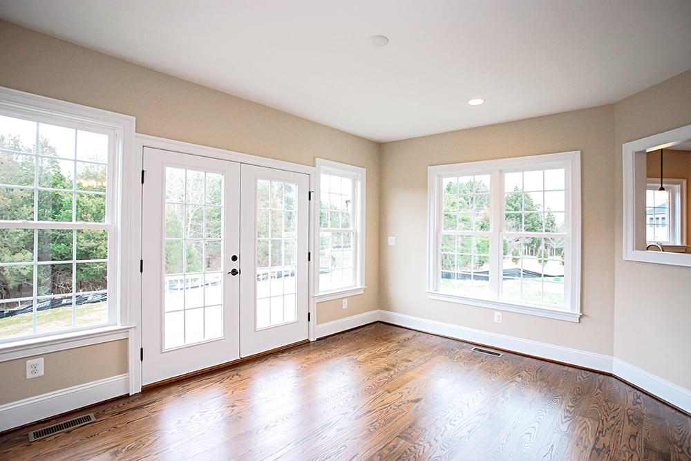 Room with many windows and glass door leading into backyard of Warrenton house