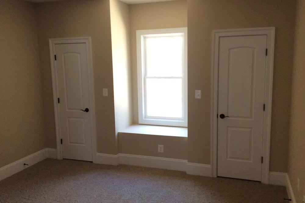 Room with two storage closets separated by window in Round Hill home
