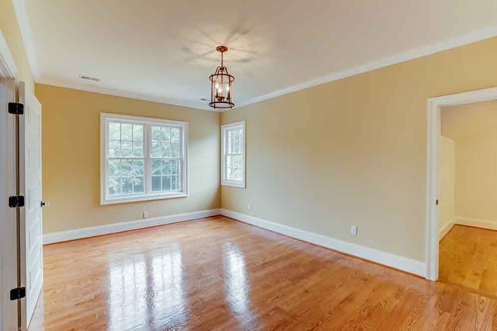 Room with windows, light brown floors, and a small lantern-looking chandelier in Middleburg home