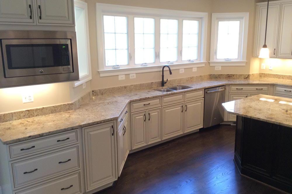 Round Hill home kitchen with sink, granite countertop, microwave, and island