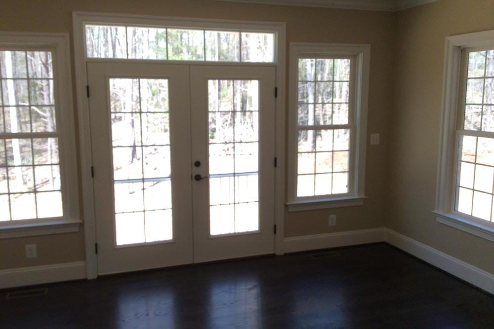 Round Hill home room with dark brown stain floors, many windows, and glass-panel double doors