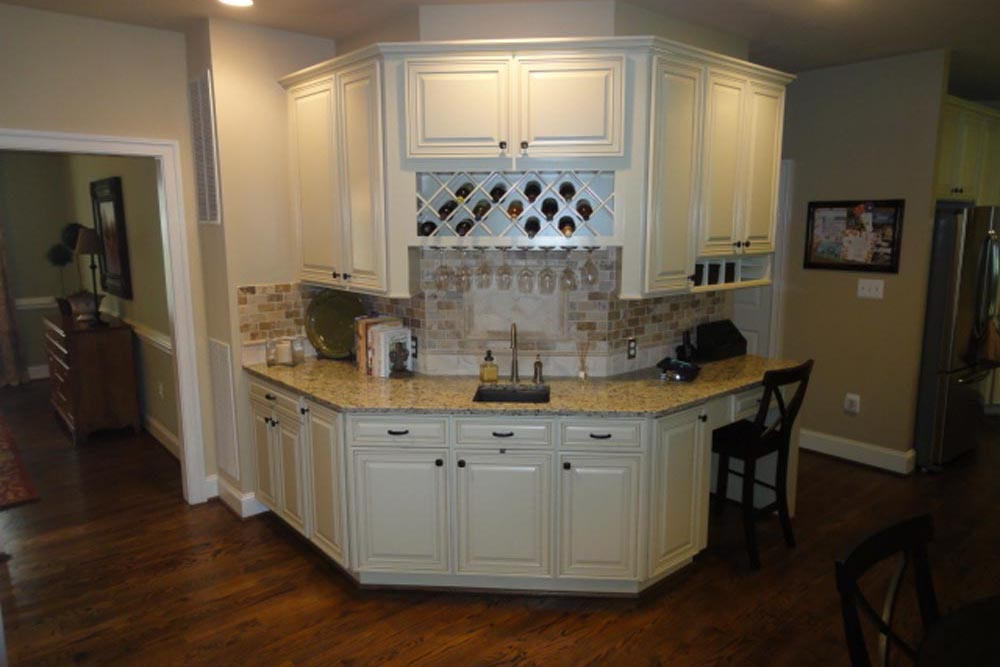 Round area in Midlands home room with white cabinets and granite countertop with sink